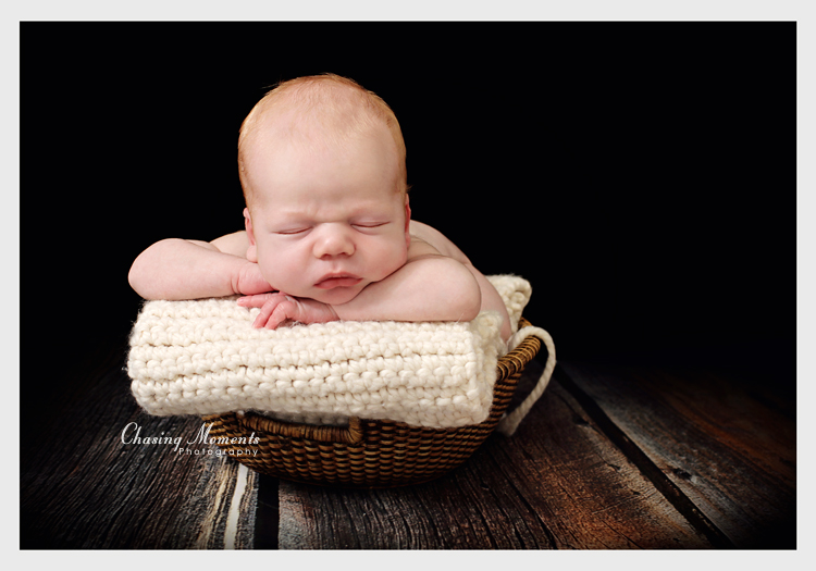 northern virginia newborn studio photography: portrait of a baby bowl in a bowl on hardwood floor asleep on a textured blanket